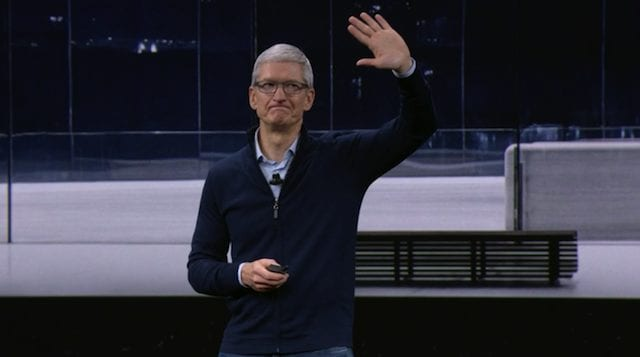 Apple CEO Tim Cook waves goodbye to the assembled press and employees