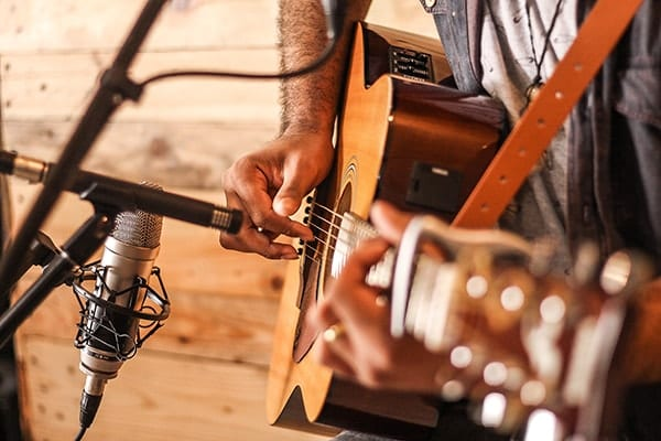 Close up image of man playing acoustic guitar with two vintage microphones