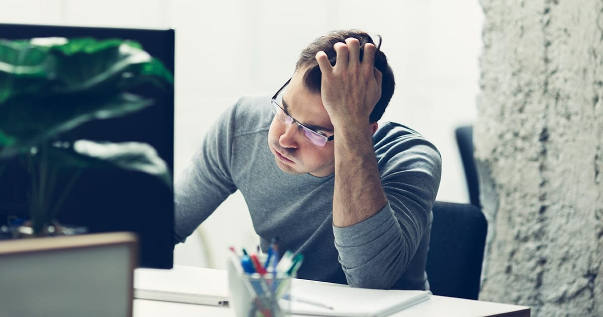 Frustrated man in front of a computer