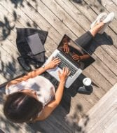 woman working outside on deck with laptop