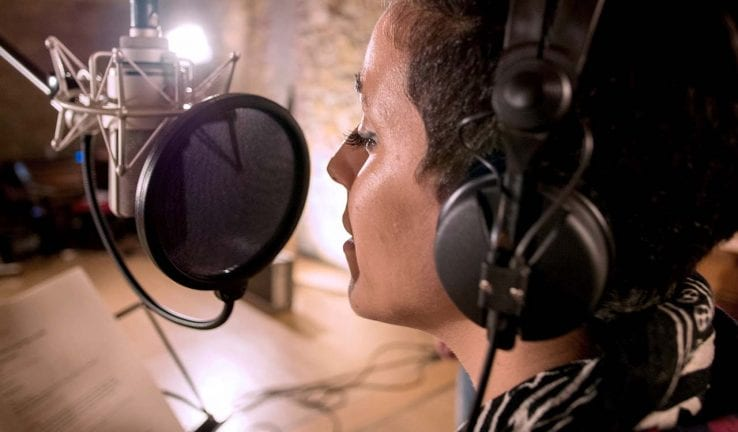 Woman singing on a microphone in a studio
