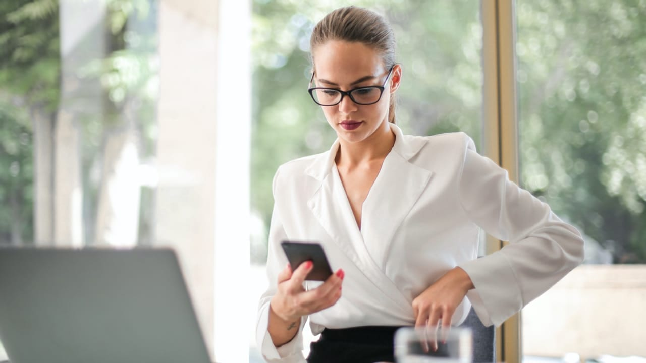 Lady in work clothes wearing glasses and blouse holding a phone in front of computer
