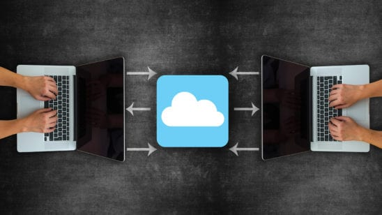 two laptops sharing data indicated by a cloud icon