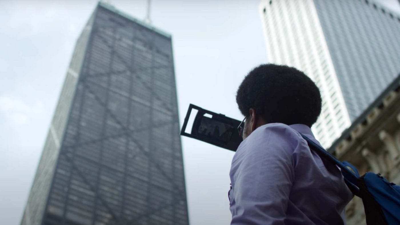 Portrait of a student filming the John hancock Center in Chicago