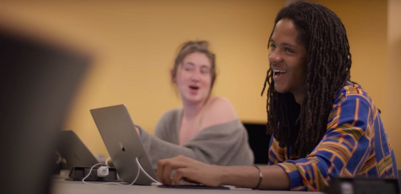 Two students smiling while creatinf content on macbook pros
