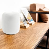 White Apple HomePod on a table next to an iPhone and iPad