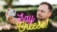 """Neon """"Say Cheese"""" with man holding camera"""