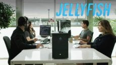 Four people sitting at a table working on editing a video with a Jellyfish Video system