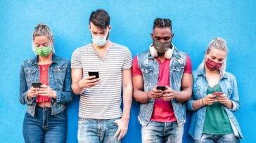 Driends with face masks using tracking app with mobile smart phones - Young millenial people sharing content on social media