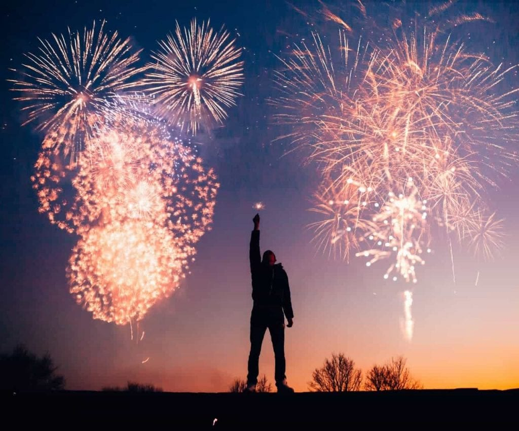 Man holding sparkler with fireworks in the background